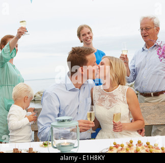Mid adult couple kissing and making a toast with group of friends - Stock Photo