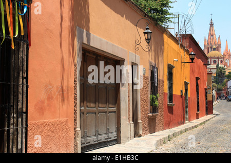 Houses lining a cobbled street with La Parroquia church in the distance in San Miguel de Allende, Guanajuato, Mexico - Stock Photo