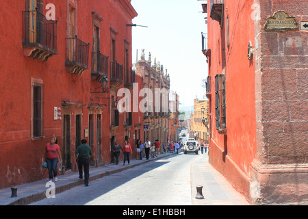 Red and orange Colonial-style buildings lining a cobbled street in San Miguel de Allende, Guanajuato, Mexico - Stock Photo