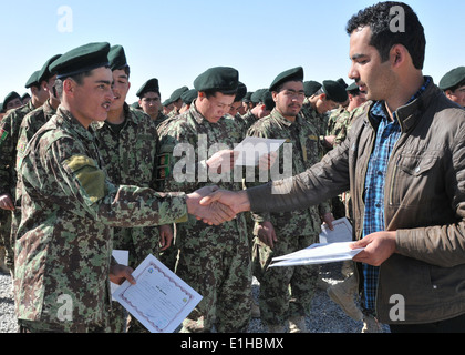 An Afghan National Army (ANA) soldier, left, receives his literacy course completion certificate at a graduation - Stock Photo