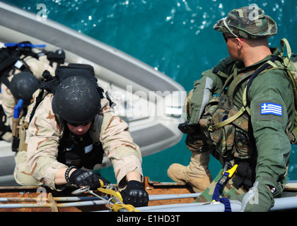 U.S. Navy Operations Specialist 3rd Class Craig Sperry, left, a boarding team member assigned to the guided missile - Stock Photo