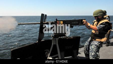 U.S. Navy Electronics Technician 3rd Class Casey Colding fires a .50-caliber machine gun aboard guided missile frigate - Stock Photo