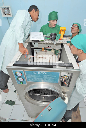U.S. Navy Hospital Corpsman 1st Class Michael Hitefield, center, checks the amperage on a sterilizer during a biomedical - Stock Photo