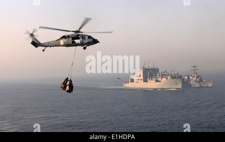 A U.S. Navy MH-60S Knighthawk helicopter assigned to Helicopter Sea Combat Squadron (HSC) 12 transports cargo from the aircraft