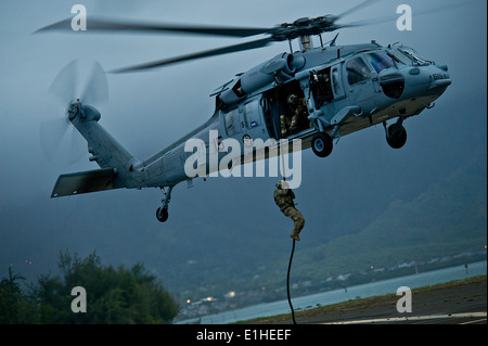 A U.S. Sailor assigned to Explosive Ordnance Disposal Mobile Unit 11 fast-ropes out of an MH-60S Knighthawk helicopter - Stock Photo