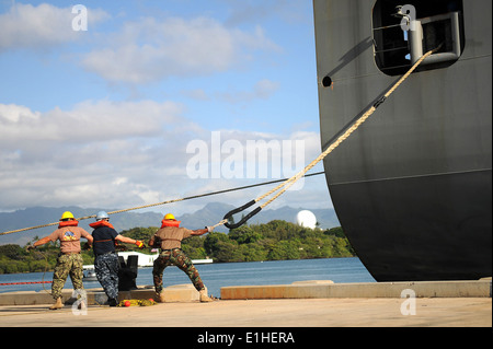 U.S. Sailors assigned to Cargo Handling Battalion 4, Air Cargo handle a mooring line from dry cargo ship USNS Matthew - Stock Photo
