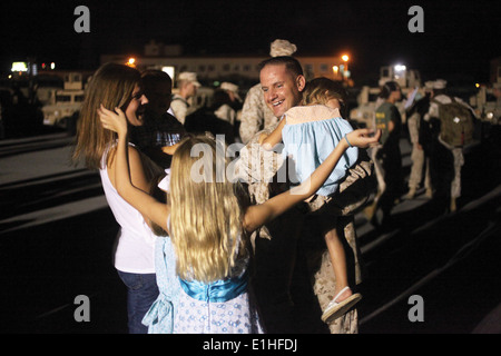 U.S. Marine Corps Master Sgt. Brannon A. Niesent is greeted at Camp Foster in Okinawa, Japan, by his family Aug. - Stock Photo