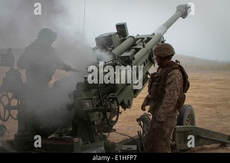 Marines serving with India Battery, 3rd Battalion, 11th Marine Regiment, swab the breach of an M777 Lightweight Howitzer after