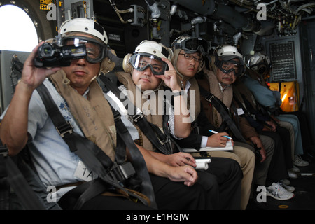 Japanese officials ride in a U.S. Marine Corps MV-22B Osprey aircraft attached to Marine Medium Tiltrotor Squadron - Stock Photo
