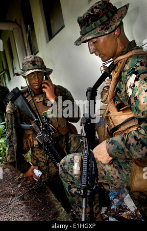 U.S. Marine Corps Lance Cpl. Clayton Climer, left, a rifleman, calls in a medical evacuation request as Staff Sgt. - Stock Photo