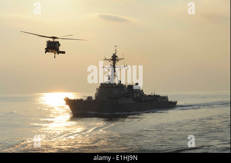 A U.S. Navy MH-60S Knighthawk helicopter assigned to Helicopter Sea Combat Squadron (HSC) 8 flies past the guided missile destr