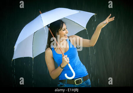 Smiling young woman holding an umbrella, enjoying the rain
