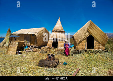 Woman of the Uro Indians in front of typical reed huts, traditional clay oven in the foreground, floating islands - Stock Photo