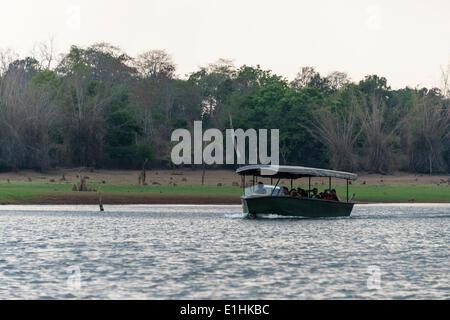 Tourists in safari boat on Kabini Reservoir, Nagarhole National Park, Karnataka, India - Stock Photo