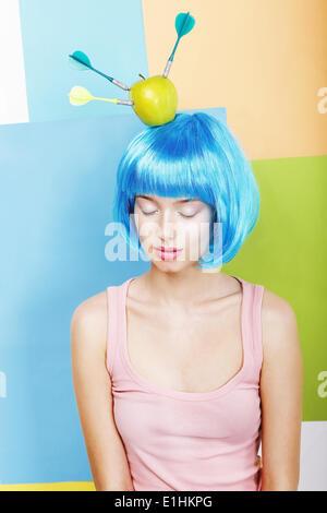 Joke. Eccentric Woman Oddball in Blue Wig with Darts and Green Apple - Stock Photo