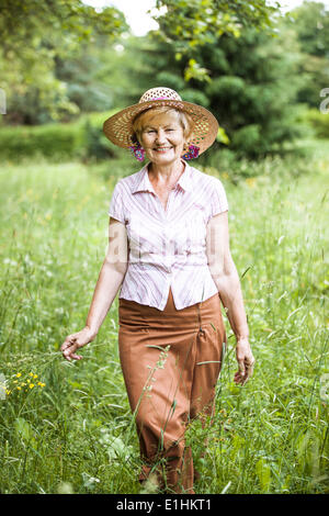 Serenity. Friendly Senior Peasant Woman in Straw in Meadow Smiling - Stock Photo