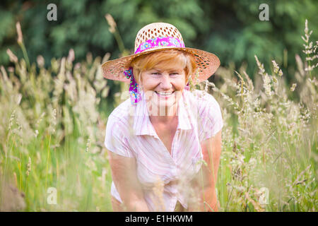 Positivity. Happy Senior Peasant Woman in Meadow smiling. Mature Friendly Lady in Bonnet - Stock Photo
