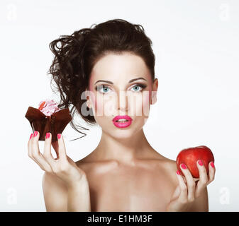 Dilemma. Diet. Undecided Woman with Apple and Cupcake - Stock Photo