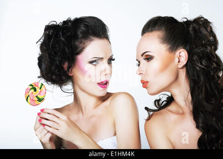 Fantasy. Woman Teasing another with Lollipop - Stock Photo