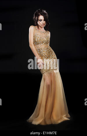 Vogue. Beautiful Fashion Model In Golden-Yellow Dress over Black - Stock Photo