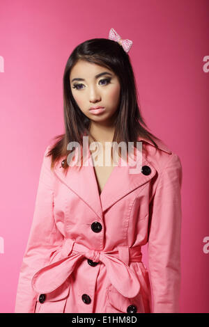 Stylish Japanese Girl in Pink Outwear over Colored Background - Stock Photo
