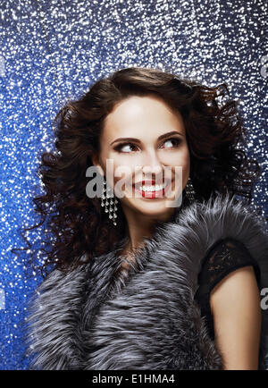 Sparkle. Beautiful Fashion Model with Shiny Earrings in Fur Vest. Toothy Smile - Stock Photo