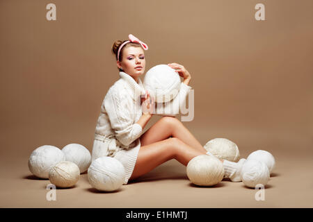 Knitting. Sewing. Woman in White Knitted Clothing with Bulk of Fluffy Clews of Yarn - Stock Photo