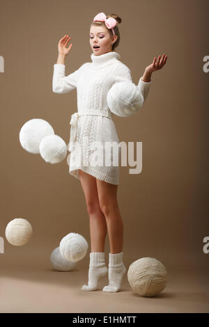 Falling Skeins. Surprised Woman in Woolen Knitted Jersey with White Balls of Yarn - Stock Photo