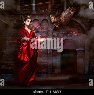 Mysticism.  Witchcraft. Sorcerer in Red Mantle with Vulture - Hawk. Ancient Scary Castle - Stock Photo
