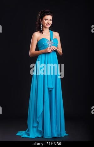 Portrait of trendy young woman in trendy blue dress smiling over black background - Stock Photo