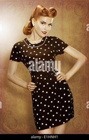 Pin-Up girl in classic fashion polka dots dress posing - grunge - Stock Photo