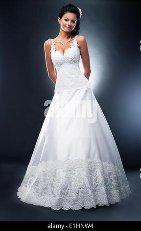 Attractive brunette model in white wedding dress with flower in her head posing in studio - Stock Photo