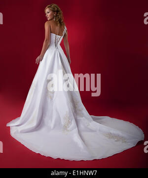 Fashionable blonde young bride in long white wedding dress over red background. Studio shot - Stock Photo