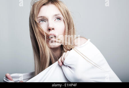 Danger - worried petty female blond hair in white cloth. No make up - series of photos - Stock Photo