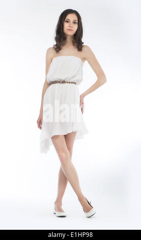Young charming female in summer dress posing over white background - Stock Photo