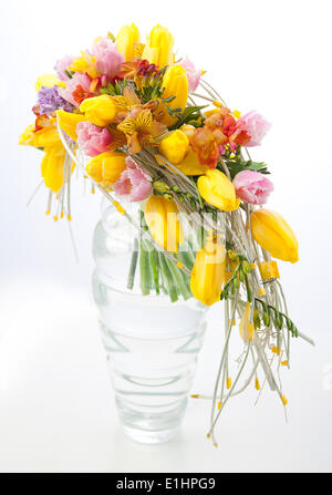 Floristry - colorful flower bouquet arrangement centerpiece in transparent vase isolated on white background - Stock Photo