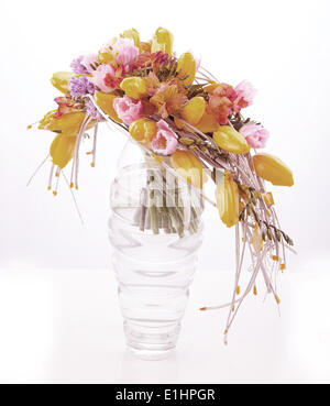 Colorful flower pattern arrangement in glass vase with yellow tulips isolated on white - Stock Photo
