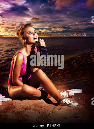 Beautiful young woman drinking booze on beach - alcoholism or other addiction - Stock Photo