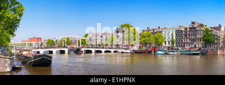 The Magere Brug ('Skinny Bridge') in Amsterdam over the River Amstel on a beautiful sunny day - Stock Photo