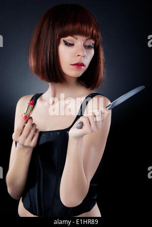 Beautiful girl in red hair wig putting on make up - reflects on table knife - Stock Photo