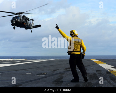 U.S. Navy Aviation Boatswain's Mate (Handling) 3rd Class Joshua Rabarabrokate directs an MH-60S Knighthawk helicopter assigned
