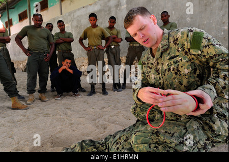 U.S. Navy Chief Master-at-Arms Neil McLean, a maritime civil affairs and security training instructor, demonstrates - Stock Photo