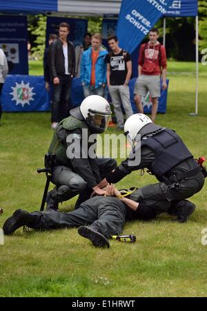 Bochum, Germany. 2nd June, 2014. Visitors look an as two police officer stage an arrest during a recruitment campaign - Stock Photo