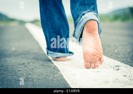 Young woman walking barefoot on centre line of empty street, partial view - Stock Photo