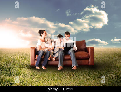 Happy family using the laptop in a field - Stock Photo