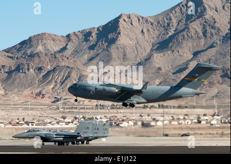A U.S. Air Force C-17 Globemaster III aircraft lands at Nellis Air Force Base, Nev., as three F-15C Eagles assigned - Stock Photo
