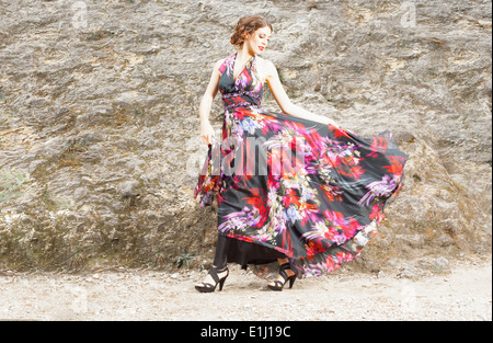 Young woman wearing silk dress with floral design - Stock Photo