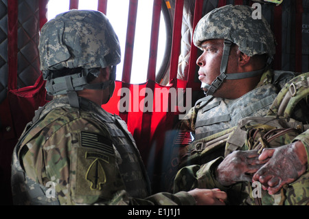 Retired U.S. Army Sgt. 1st Class Jose Mendez and Sgt. Omar Avila look out of a CH-47 Chinook helicopter during Operation - Stock Photo