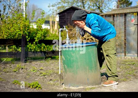 Man washing himself in the garden - Stock Photo
