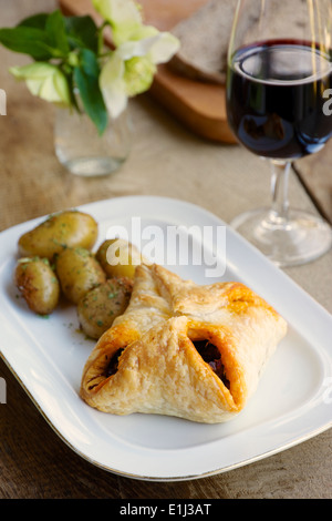 Puff pastry parcels with a chestnut mushroom filling, potatoes and a glass of wine - Stock Photo